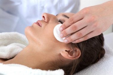 Woman during facial cleansing in spa