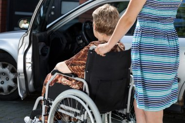 Woman carrying lady in a wheelchair
