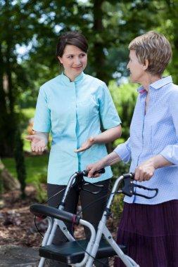 Nurse encourages older woman for walking