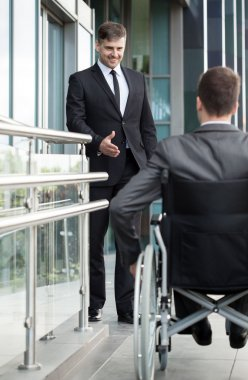 Businessman greeting the disabled man