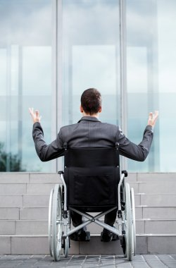 Disabled man in front of stairs