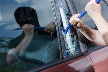 Robber with crowbar smashing glass