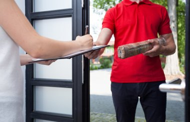 Woman receiving a package from delivery man