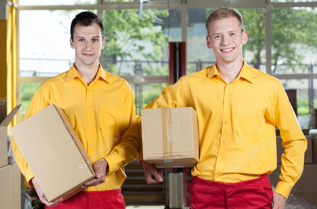 Storekeepers holding boxes in warehouse