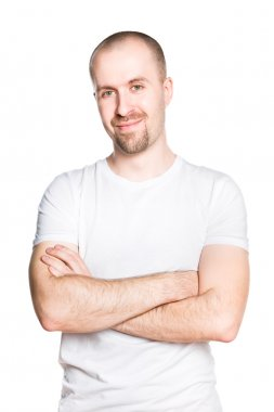 Handsome smiling young man with folded arms in white t-shirt isolated on white