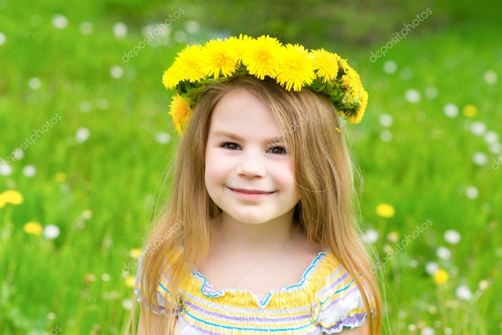 Portrait of a beautiful blond little girl with a floral head wreath