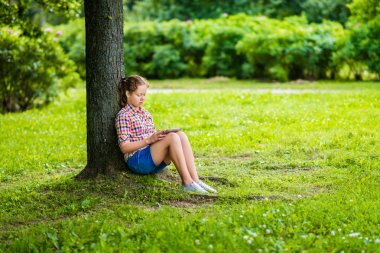 Pretty teenager girl in casual clothes with digital tablet on her knees in the park under the tree