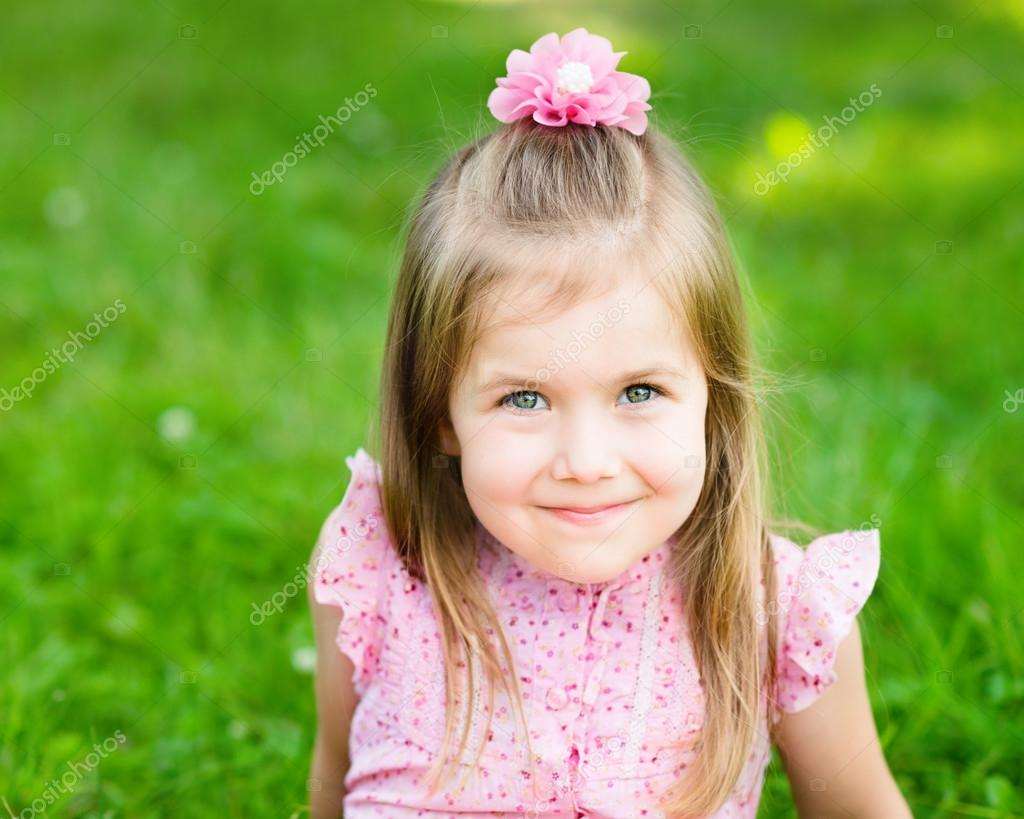 Sweet smiling little girl with long blond hair, sitting on grass in summer park, closeup outdoor portrait
