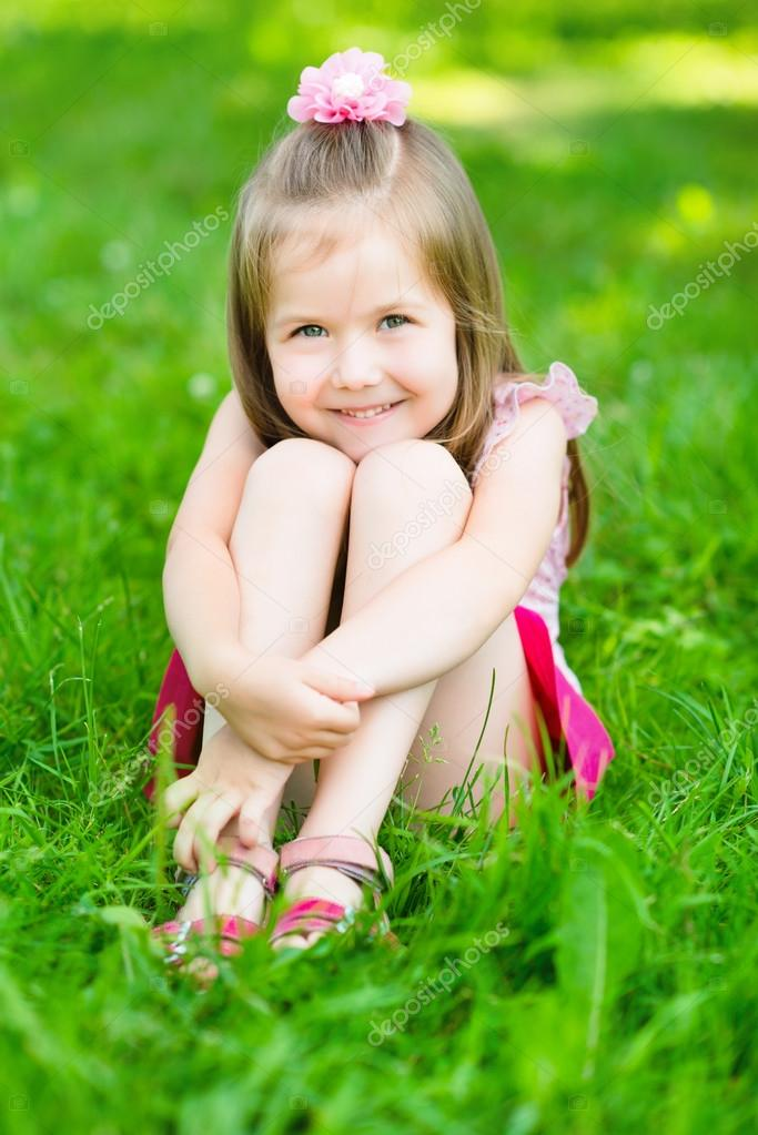 Cute little girl with long blond hair sitting on grass in summer park putting her hands around - Pics of small little girls ...