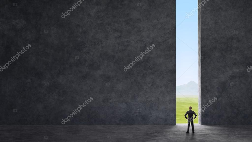 businessman standing between the gray walls and looking at the nature outside