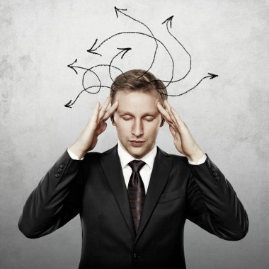Young businessman thinking with arrows on his head