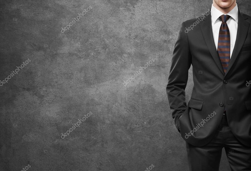 man in suit on a dark concrete wall background