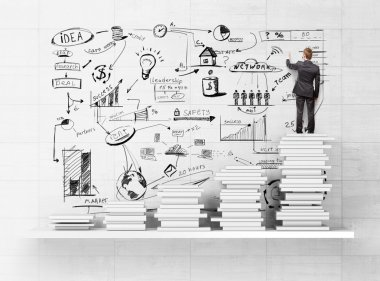 Businessman standing on books and drawing strategy