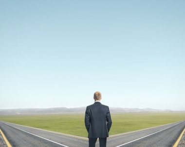 Businessman standing in front of two roads