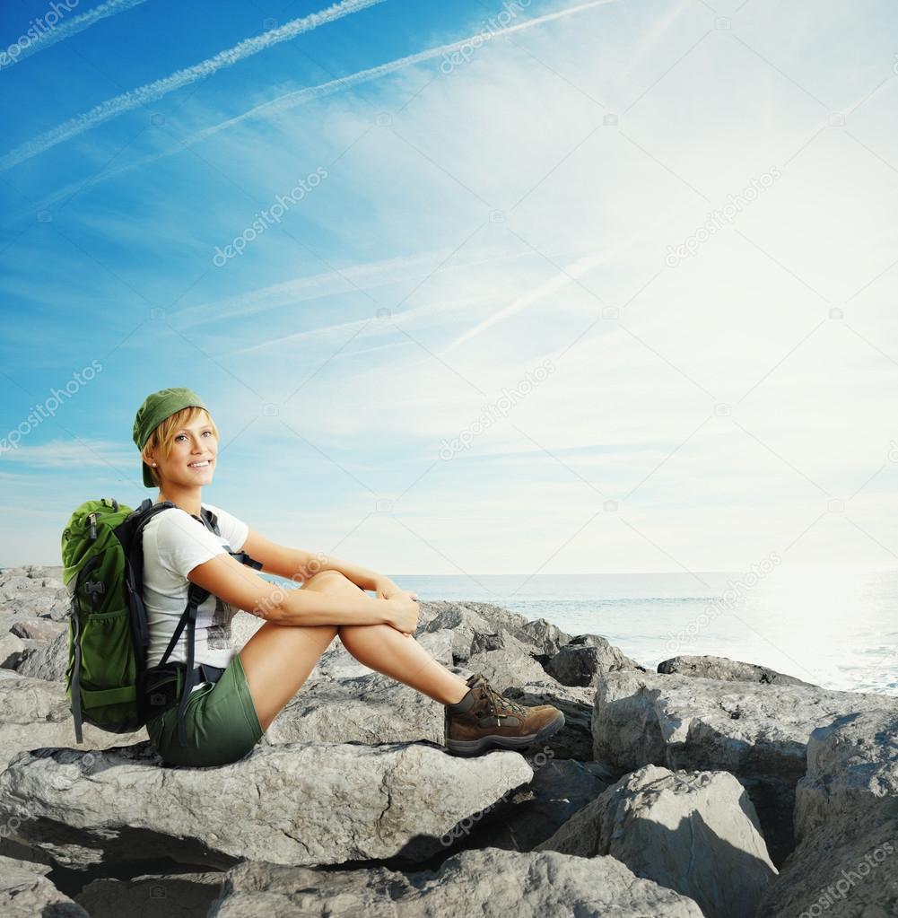Traveler woman sitting on a rocks