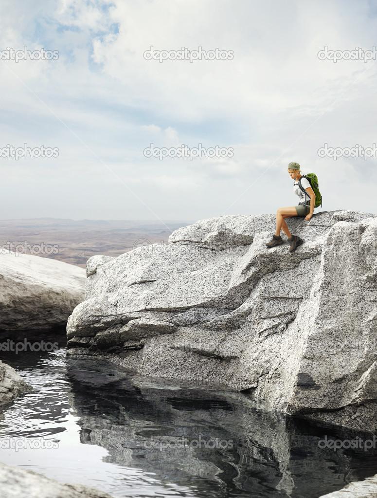 Traveler girl sitting on a rock