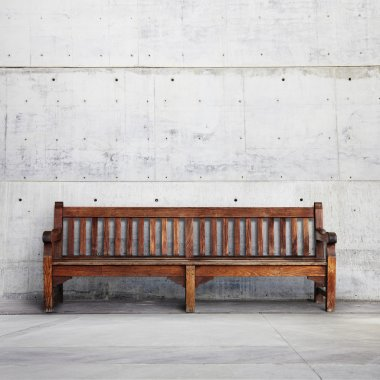 Wooden bench against a wall building