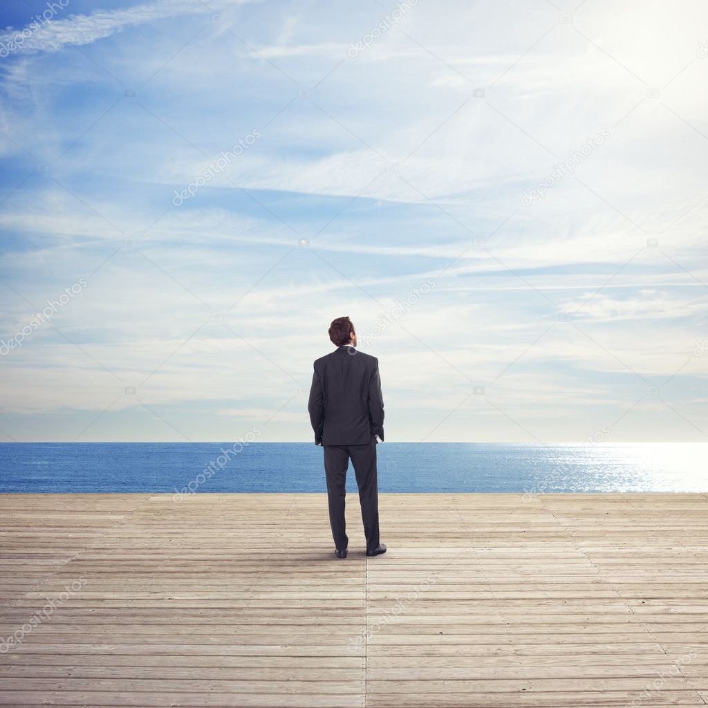 Business man standing on a pier