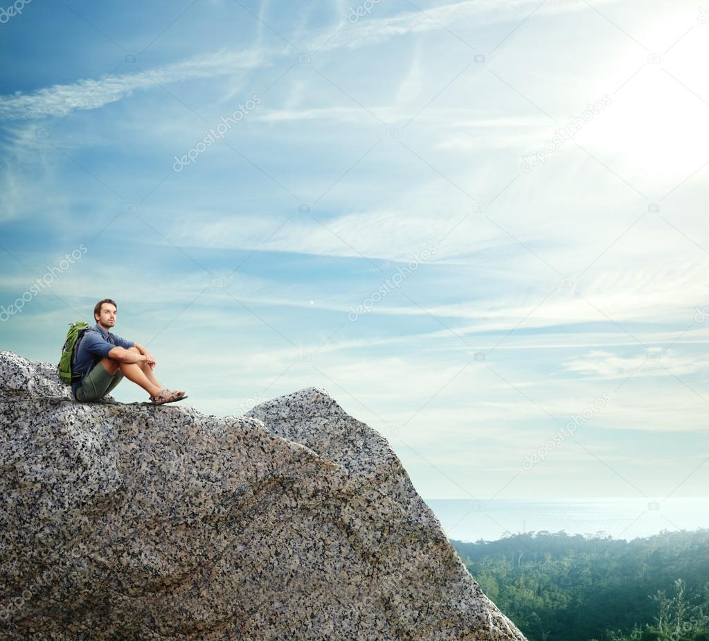 Young man sitting on a rock