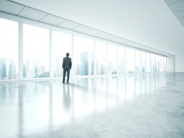 Businessman standing in empty bright office and look at city