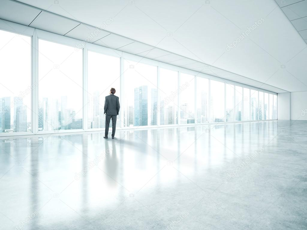 bright office. businessman standing in empty bright office and look at city u2014 photo by kantver t