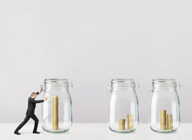 Businessman push the glass jars with coins