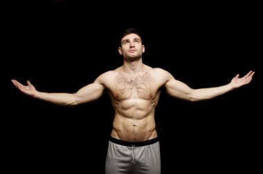 Topless man stood with his arms outstretched