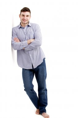 Handsome man leaning against a white wall