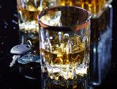 Autoschlüssel im Vordergrund und ein Glas Whisky