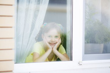 Smiling girl looks in a window