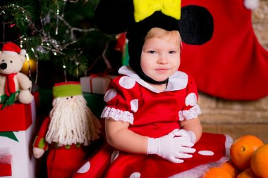 A little girl dressed as a mouse near the Christmas tree with gifts
