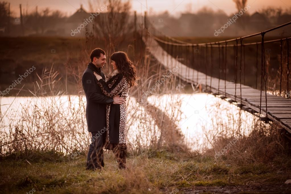 Young lovers near the rope bridge across the river