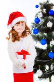 Fotografia bambina con regalo vicino allalbero di Natale