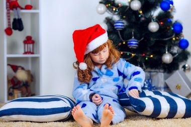 Child in pajamas near the Christmas tree