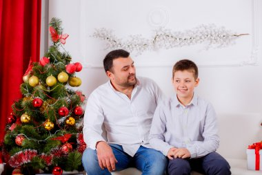 Happy dad and son near the Christmas tree