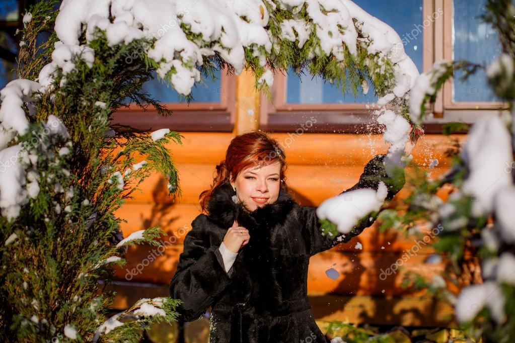 Girl removing snow from fir tree branches