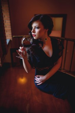 Girl in the  evening dress drinking wine