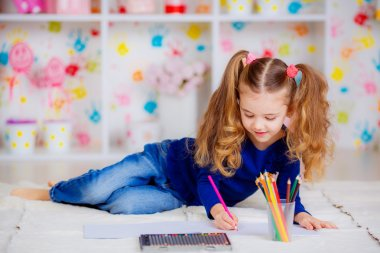 Happy little girl draws with colored pencils