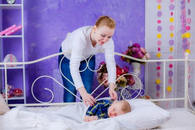 Mother putting her newborn baby to sleep