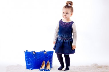 Little girl with shoes and bag of mom