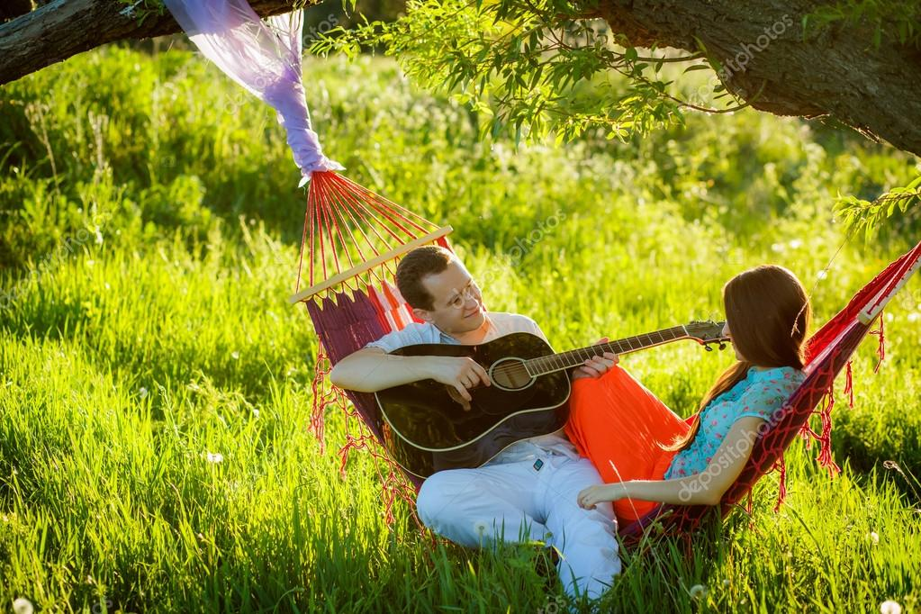 Couple in  hammock playing the guitar.