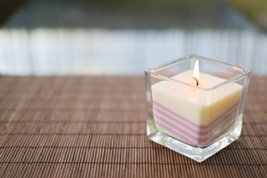 Pink burning candle on table composition