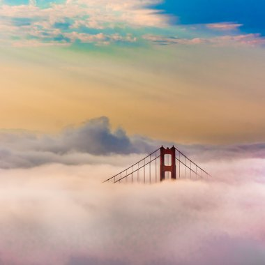 World Famous Golden Gate Bridge Surrounded by Fog after Sunrise in San Francisco,Californiaa