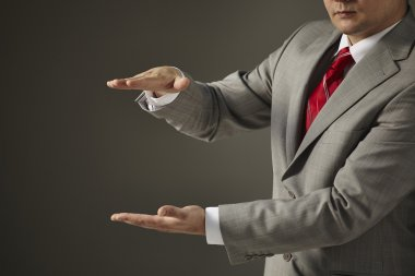 Businessman in a gray suit shows the size of the hands