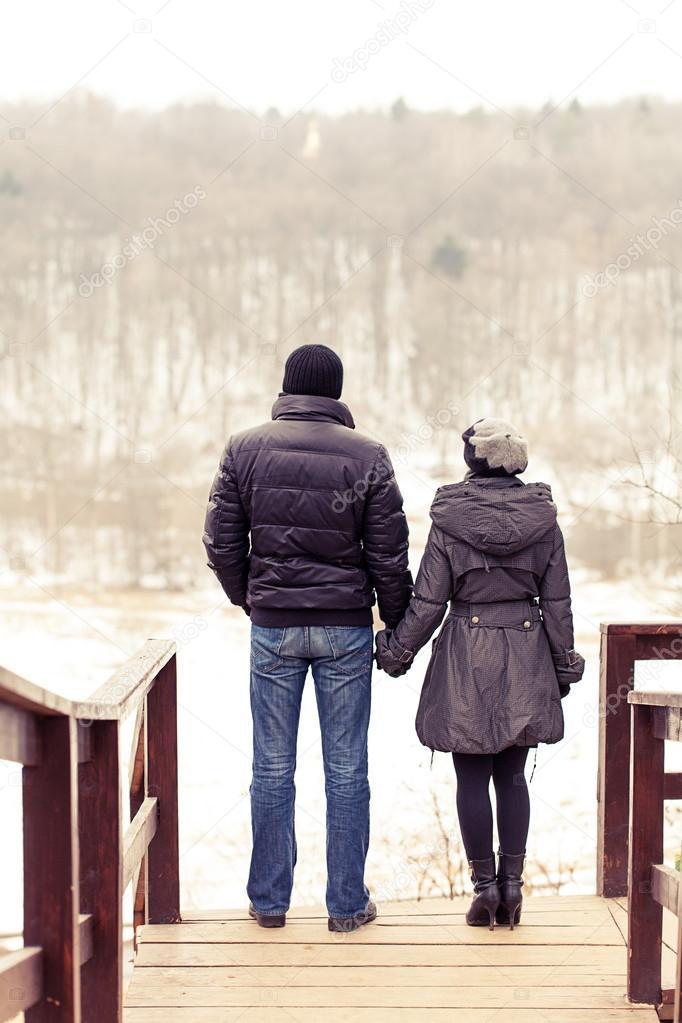 Couple in winter park on the bridge