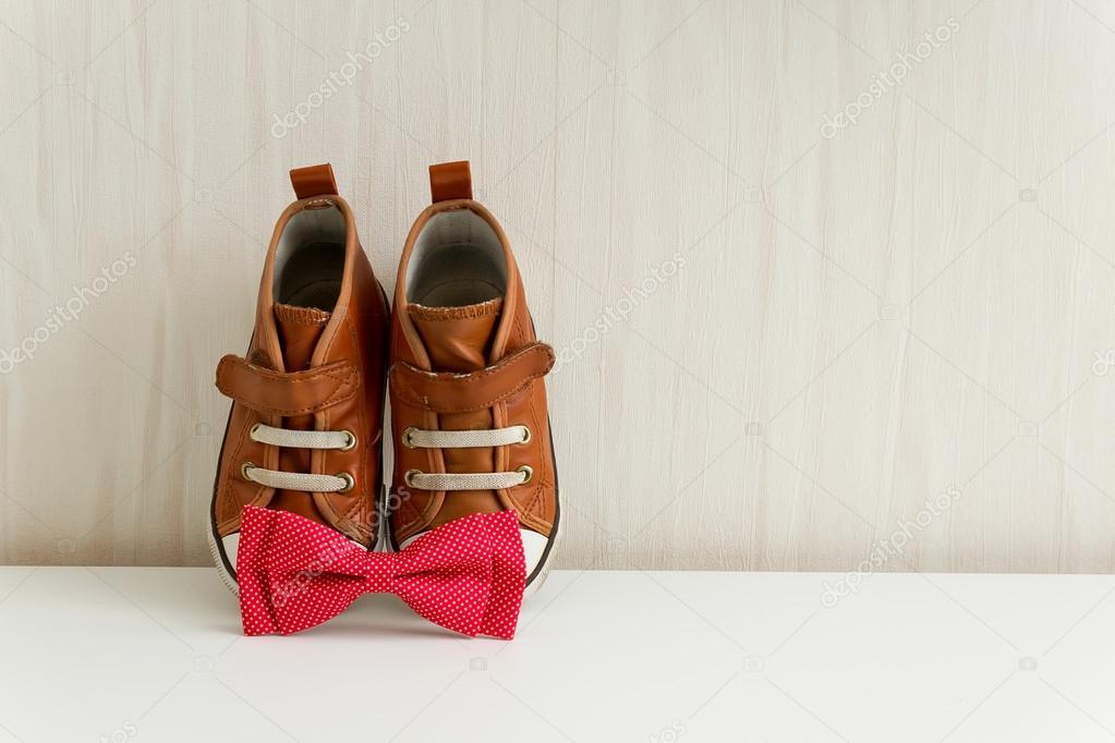 Fliege und Schuhe auf Hintergrund Wand mit Tapete. braune Turnschuhe und  rote Fliege mit Polka dot — Foto von annakukhmar 10cd41e1a1