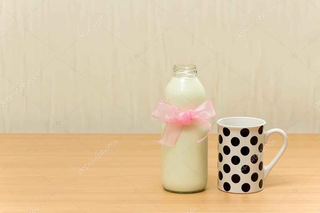 Behang Met Stippen : Kruik van melk en een kopje met stippen op houten tafel over behang