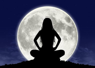 young woman in meditation at the full moon