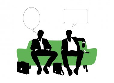 Two businessmen speaking seated on green sofa
