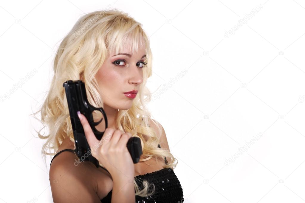 Young woman secret agent in long black dress posing with gu stock photo